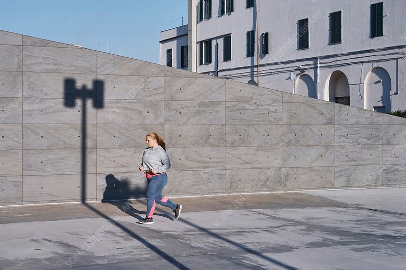 Curvaceous young female runner running along sidewalk