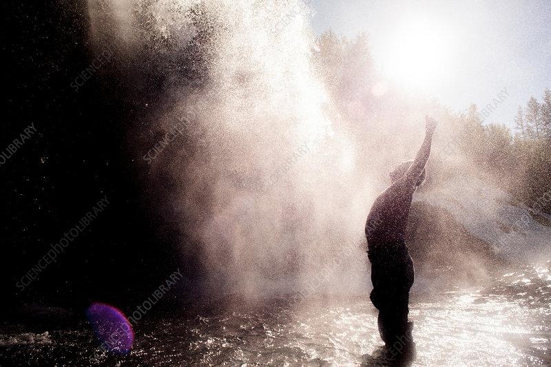 Man enjoying waterfall spray, Ural, Sverdlovsk, Russia