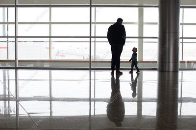 Father and son beside window at airport, Alberta, Canada