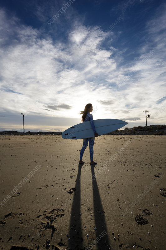 Young female surfer on beach, backlit, Spain