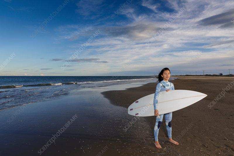 Portrait of female surfer standing on beach, Spain