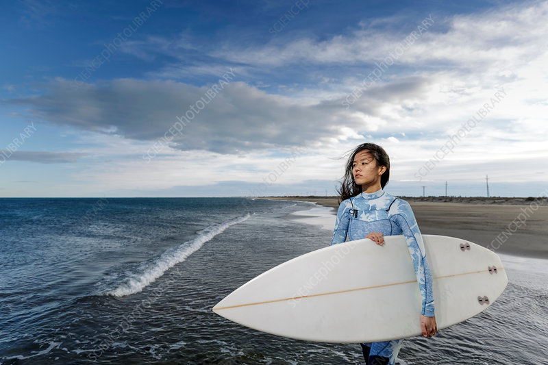 Young female surfer on beach, Tarragona, Catalonia, Spain