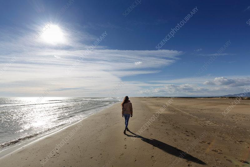 Rear view of woman strolling along on beach, Spain