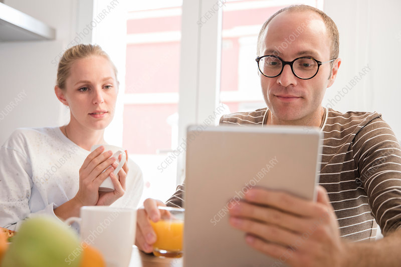 Young woman and boyfriend looking at digital tablet