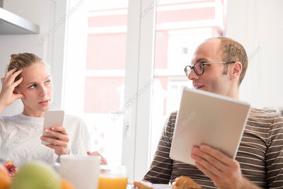 Young woman and boyfriend holding smartphone