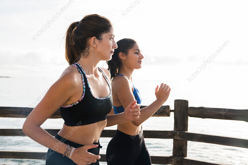 Two female runners running on sea waterfront, Spain