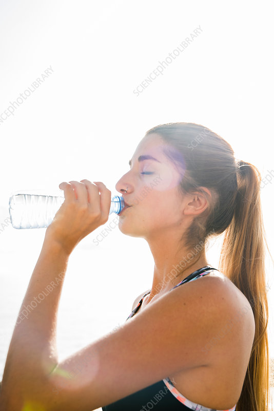 Young woman training, drinking bottled water