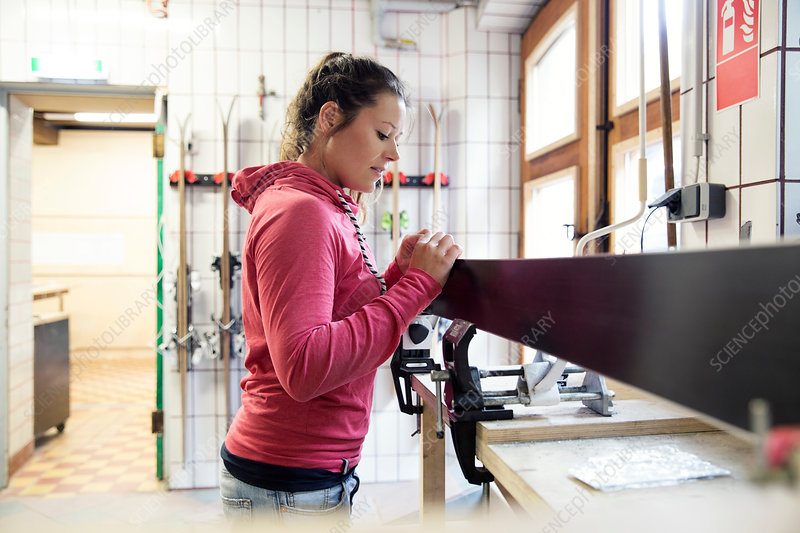 Woman in workshop, inspecting ski equipment