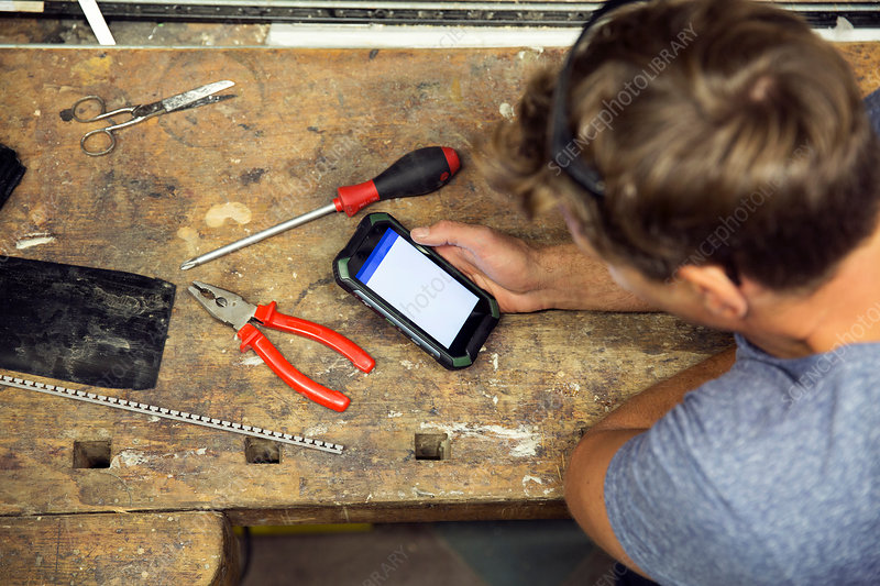 Man in workshop, using smartphone, overhead view