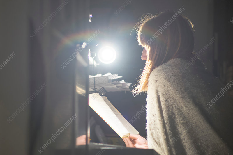 Woman reading at desk by table lamp