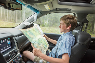 Boy on road trip reading map