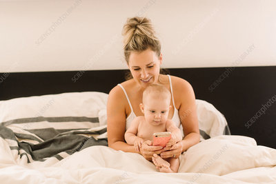 Baby girl and mother looking at smartphone