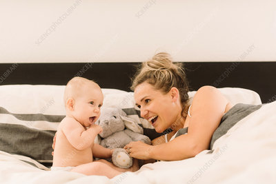 Woman lying in bed playing with baby daughter