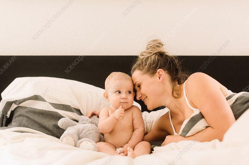 Woman lying in bed with arm around baby daughter