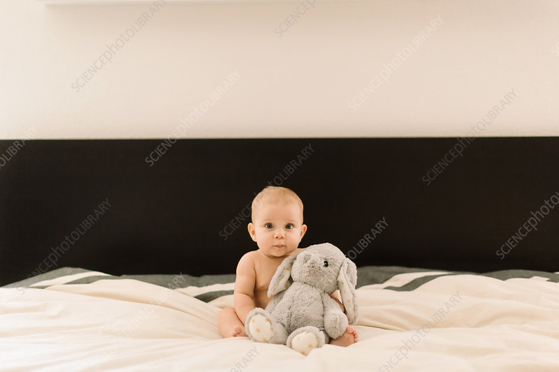 Portrait of cute baby girl sitting up on bed with soft toy