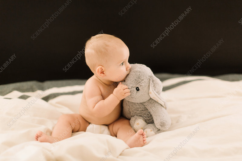 Cute baby girl sitting up on bed with soft toy