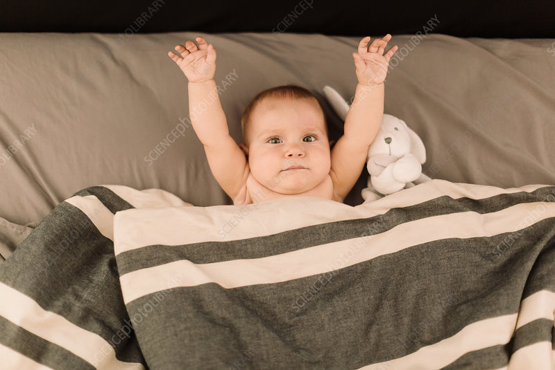 Portrait of baby girl lying in bed with arms raised