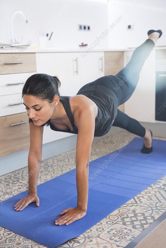 Woman doing exercise on mat on kitchen floor
