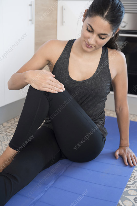 Woman doing exercise on mat on kitchen floor