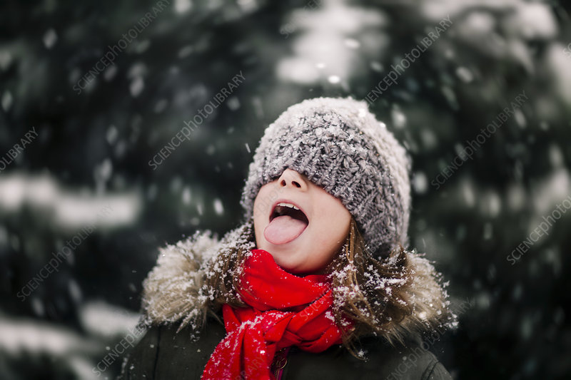 Portrait of girl catching falling snow on tongue