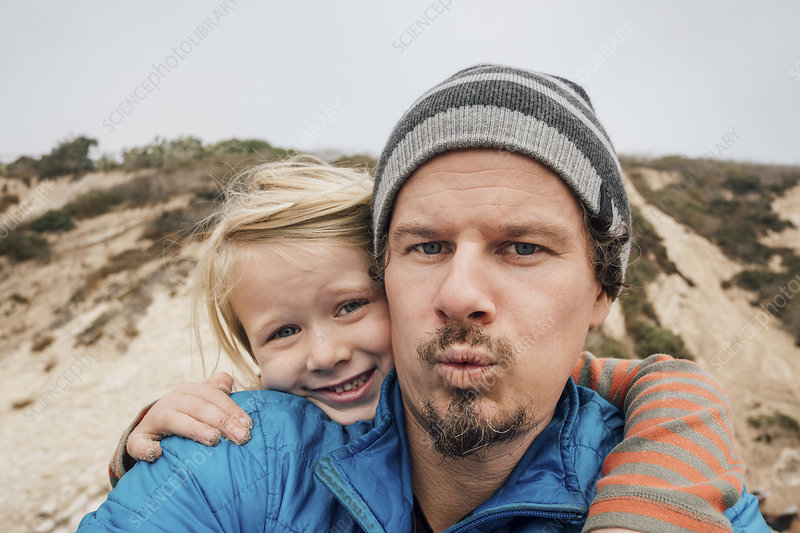 Portrait of father and son, outdoors, smiling, close-up