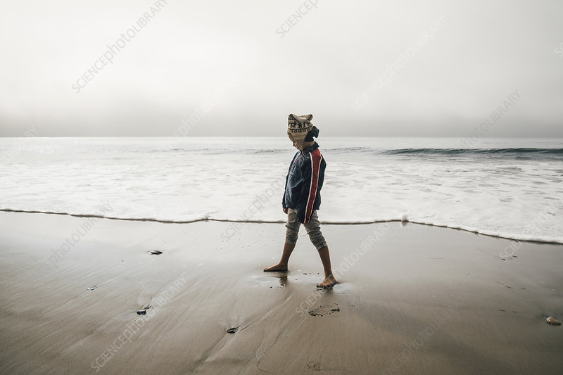 Young boy standing on beach, looking away
