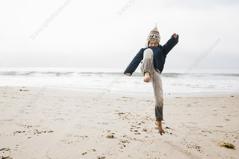 Young boy on beach, jumping, mid air
