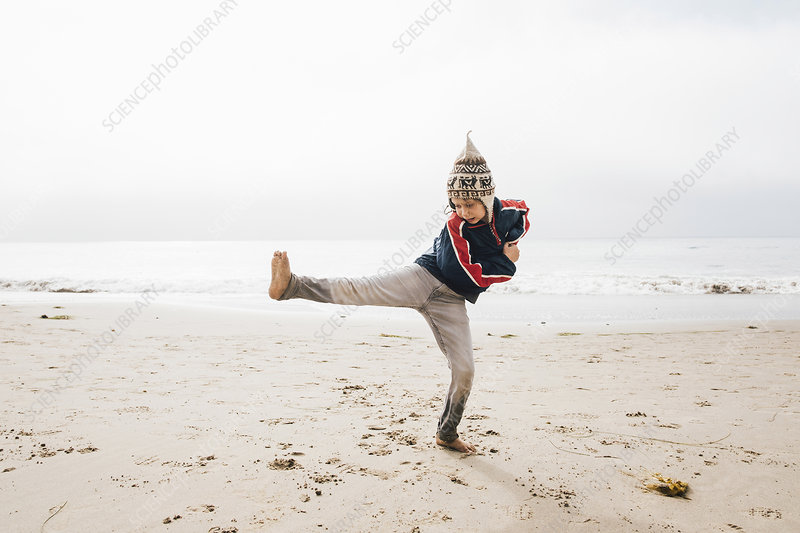 Young boy standing on beach,balancing on one leg