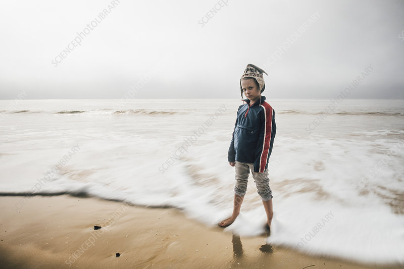 Portrait of boy standing on beach, pensive expression