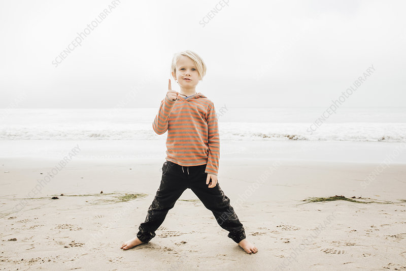 Portrait of young boy on beach, finger raised