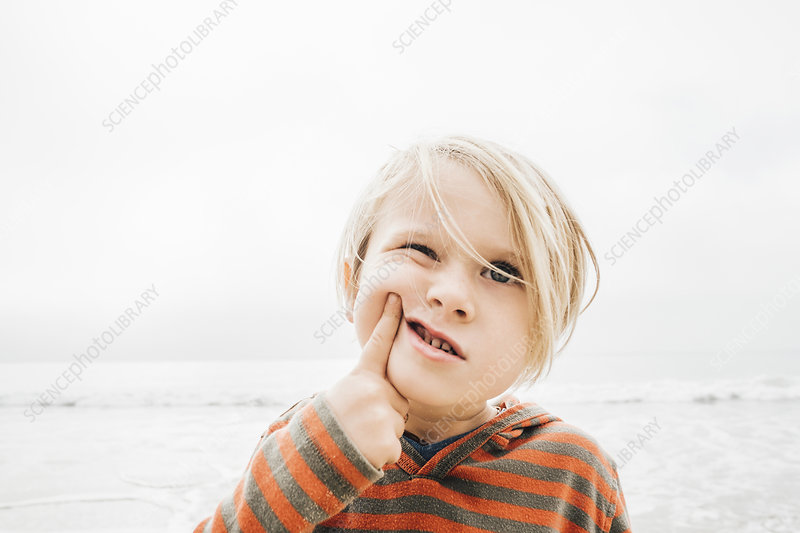 Portrait of boy on beach, finger on face, making faces