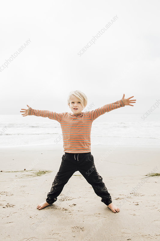 Portrait of young boy on beach, arms outstretched