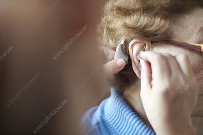 Woman helping senior woman insert hearing aid