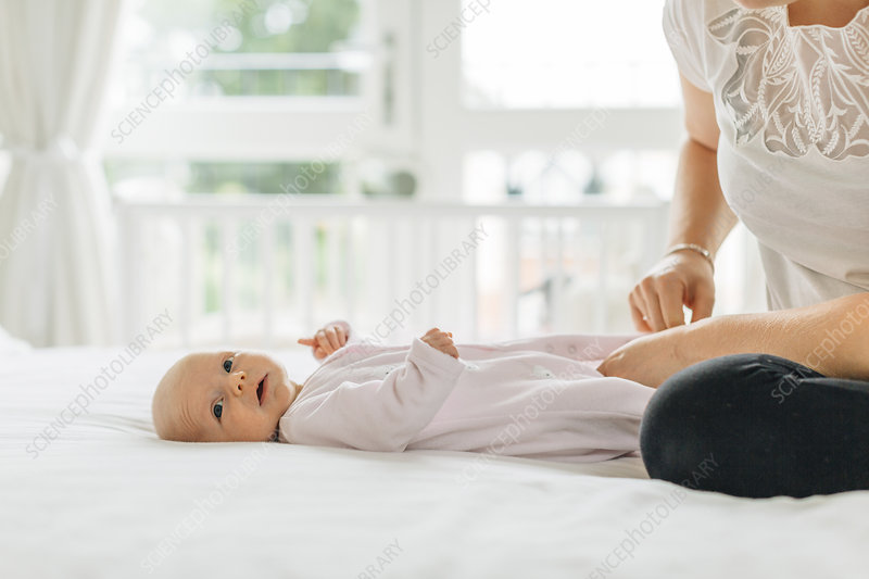 Young woman dressing baby daughter on bed, cropped
