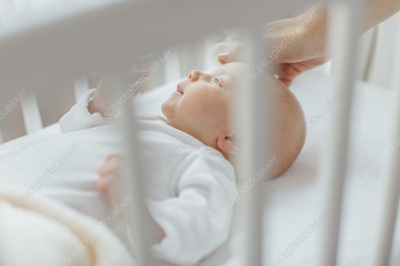 Baby girl lying in crib, mother's hand soothing head