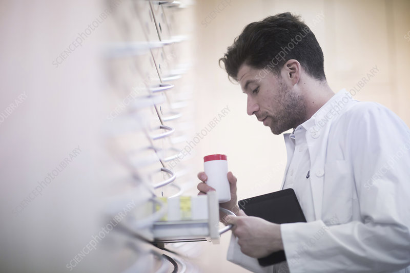 Young male pharmacist taking pill bottle