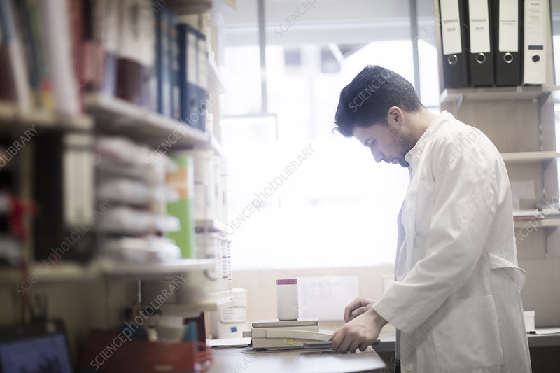 Young male pharmacist weighing pill bottle