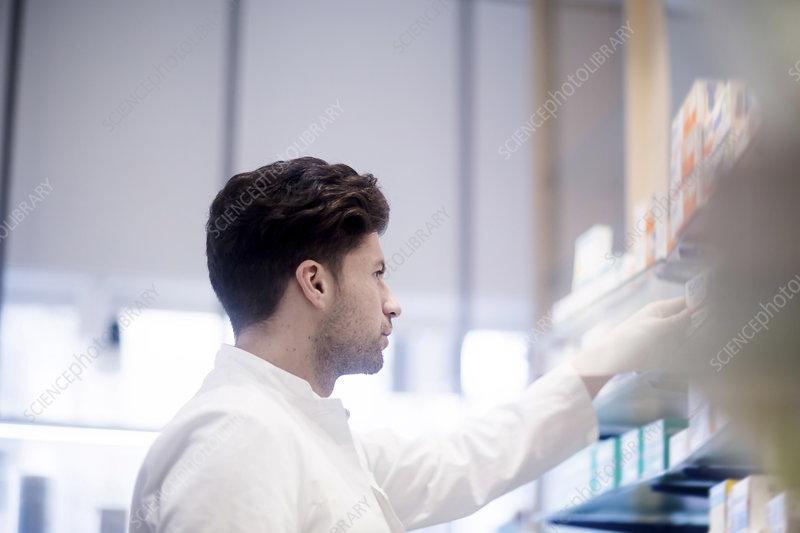 Pharmacist removing medical drug from pharmacy shelves