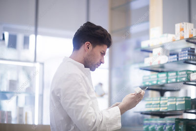 Young male pharmacist reading medical drug packet