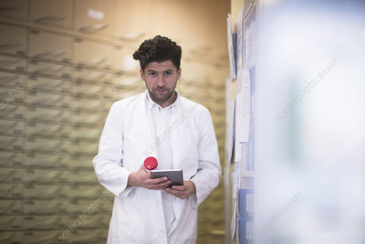 Portrait of male pharmacist using digital tablet