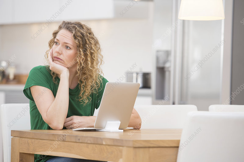 Woman sitting, laptop in front of her