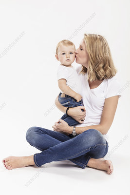Woman sitting on floor kissing baby son