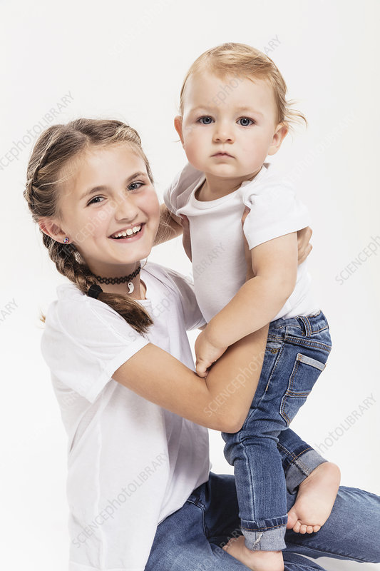Studio portrait of kneeling girl holding baby brother