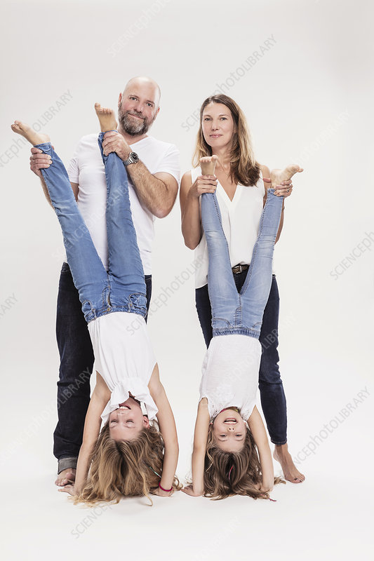 Mature couple with two daughters doing hand stands