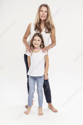 Studio portrait of mature woman with daughter, full length