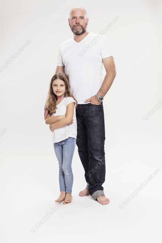 Studio portrait of mature man with daughter, full length