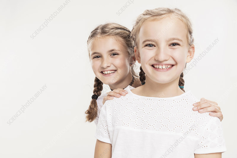 Studio portrait of two smiling girls, head and shoulders