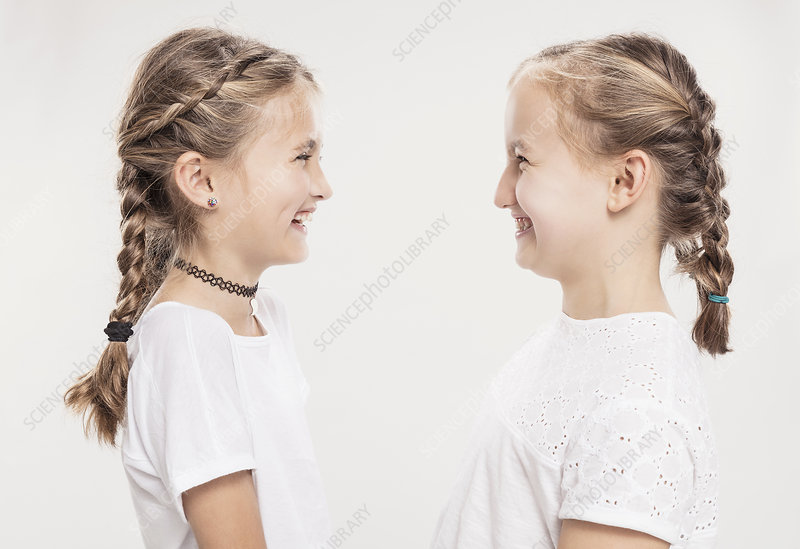 Two girls with hair plaits face to face