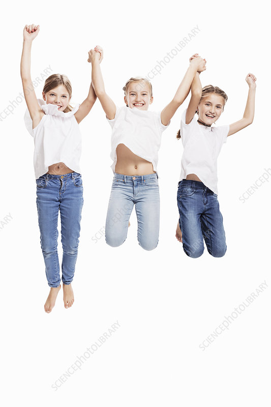 Studio portrait of three girls jumping mid air