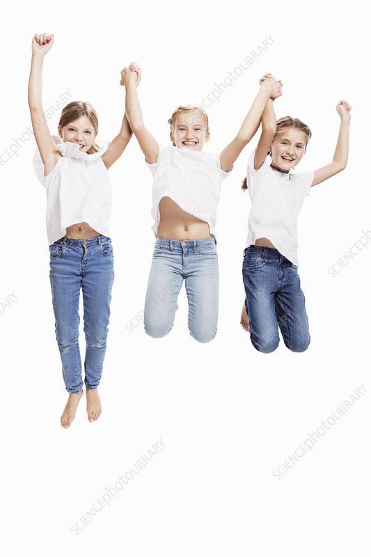 Studio portrait of three girls jumping mid air
